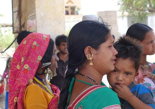 A woman breaks down as she is about to board a bus for Mumbai leaving her son behind.