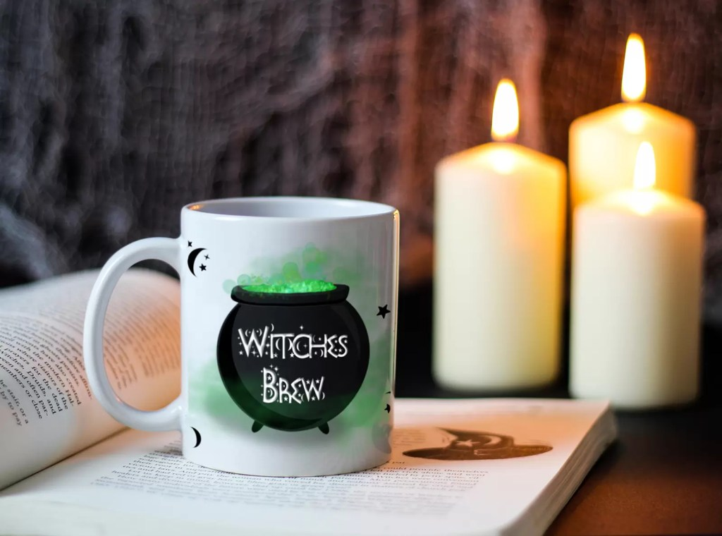 White ceramic mug with the illustration of a green and black cauldron saying witches brew