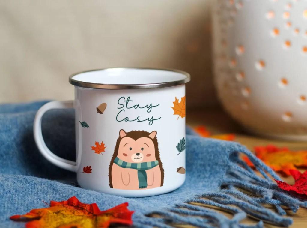 autumn enamel mug design of a cute hedgehog wearing a scarf