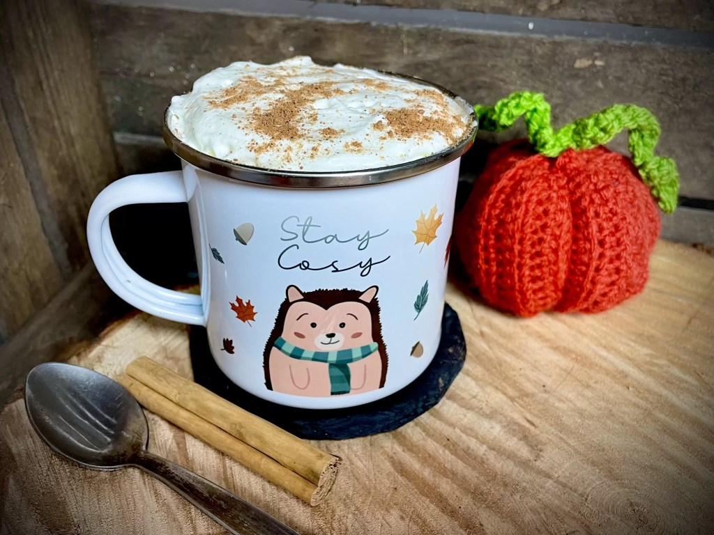 White enamel mug filled with pumpkin spice latte topped with cream and grated cinnamon