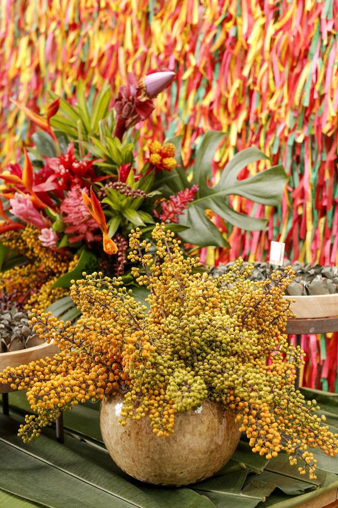 arranjo com flores tropicais e sementes em vasos de cerâmica