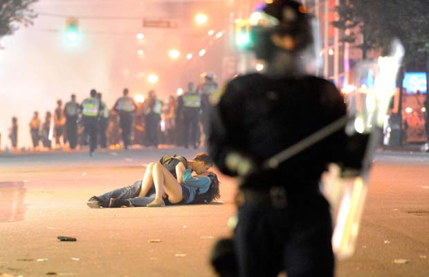 Riot police walk the street as a couple kiss on June 15, 2011 in Vancouver, as the city broke out in riots, following the Vancouver Canucks loss in game seven of the Stanley Cup Finals.