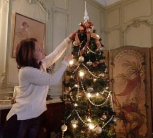 Valerie Meskoures of the Centerport Garden Club adjusts ribbons on a tree in Rosamund Vanderbilt's bedroom