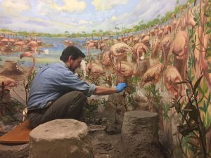 Artist Sean Murtha repairs large painting