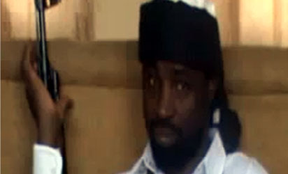"""Abubakar Shekau, the leader of Nigeria's Boko Haram Islamist militants, dressed in a black turban and a white gown and bullet-proof vest - holding an AK 47 rifle. In his 40-minute audio message, Shekau reportedly  blamed the deaths of """"innocent civilians"""" on Nigeria's security forces but threatened to carry out a bombing campaign against Nigeria's secondary schools and universities - unless security forces stopped what he claimed was a series of recent attacks on Islamic schools or madrassas in the northern town of Maiduguri.AFP PHOTO / YOUTUBE"""