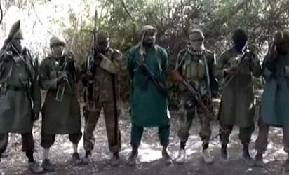 A picture taken from a video distributed to journalists in recent days through intermediaries and obtained by AFP on March 5, 2013 reportedly shows Abubakar Shekau (C), the suspected leader of Nigerian Islamist extremist group Boko Haram, flanked by six armed and hooded fighters in an undisclosed place.