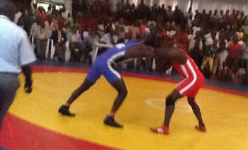 Delta state's Lucky Opiated in blue outfit lucks hornets with Adibo Dick of Bayelsa state in the men's 84kg weight class free style at the just concluded Maiden Chief E K Clerk wrestling championship in Warri, Delta state. Adibo Dick won the bout.