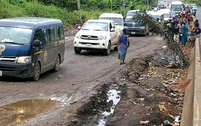 *Slow-moving traffic on the  pothole-ravaged road