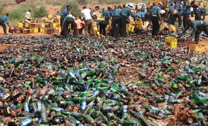"""Sharia enforcers called Hisbah destroy thousands of bottles of beer outside northern Nigeria's largest city of Kano on November 27, 2013. The Hisbah destroyed over 240,000 bottles of beer along with over 8,000 litres of local brew called """"Burukutu"""". AFP"""