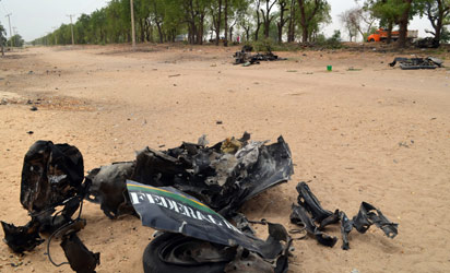 NIGERIA, Maiduguri : A picture shows the wreckage of a police van that was targeted suspected Boko Haram militants in Nigeria's troubled northeastern city of Maiduguri on March 25, 2014, killing five police officers. A vehicle approached the parked van and an explosive was thrown towards it, with the blast killing all the officers inside as well as the three attackers. AFP PHOTO