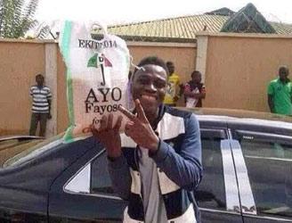An Ekiti State University student displaying a bag of rice he got from Ayo Fayose