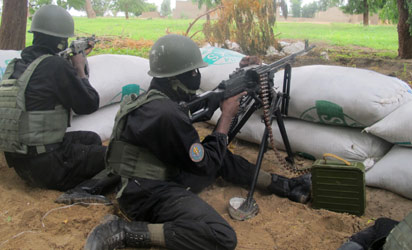 CAMEROON, Amchide : This photo taken on June 17, 2014 in the border town of Amchide, northern Cameroon, shows police forces of the multi-purpose intervention brigade holding a surveillance position, as part of a reinforcement of its military action against Nigerian Islamist group Boko Haram.