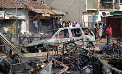People look at the burnt out shell of a car following an explosion on July 23, 2014 in Kaduna, north of Nigeria. A second blast today in the city has killed at least 17 people, the national rescue agency said, after an earlier suicide attack in the city killed at least 25. An around-the-clock curfew was announced for the city after the bombings. AFP PHOTO