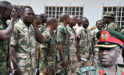 Soldiers accused of mutiny tasked with fighting Boko Haram militants in Abuja on October 2, 2014. Nearly 100 soldiers tasked with fighting Boko Haram militants in Nigeria's far northeast appeared at a military court martial on Thursday, facing a range of charges including mutiny. The hearing comes just weeks after a tribunal sentenced 12 soldiers to death following their conviction for shooting at their commanding officer in the Borno state capital, Maiduguri, in May. AFP PHOTO INSET President of the Court Martial, Brigadier General. Musa Sain Yusuf