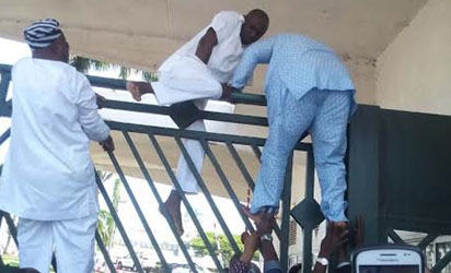 Police attack at National Assembly: Lawmakers scaling gate of National Assembly as Police blocked National Assembly gate in Abuja. Photo by Gbemiga Olamikan