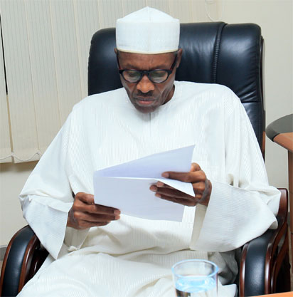 """President-elect Muhammadu Buhari reviews a document in Abuja on April 1, 2015. Nigeria's new president-elect Muhammadu Buhari hailed polls that will lead to the first democratic change of power in Africa's most populous nation as """"historic"""" hours after he secured a decisive victory. AFP PHOTO"""