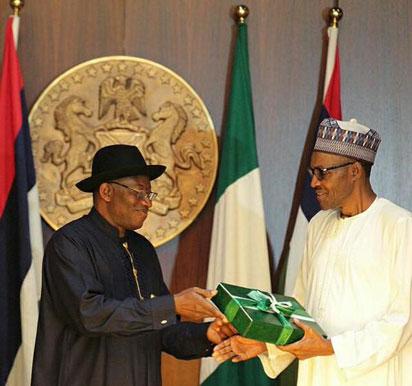 Handover :  Jonathan presenting handing over notes to Buhari.
