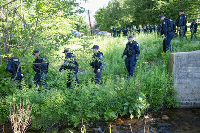 CHASM FALLS, NY - JUNE 26: Correction officers head into the woods as the manhunt for convicted murderers Richard Matt and David Sweat continues on June 26, 2015 in Chasm Falls, New York. Matt and Sweat were discovered missing from a prison in nearby Dannemora on June 6.   Scott Olson/Getty Images/AFP