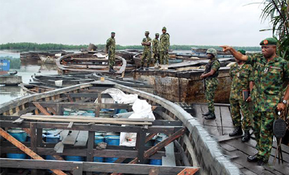 OIL THEFT —Commander, 2 Brigade, Nigerian Army, Port Harcourt, Brig.-Gen. Stevenson Olabanji (right) and other officers, during a raid on an illegal oil bunkering site discovered on Nigerian Ports Authority Road in Port Harcourt, Tuesday. Inset: About 5,150 drums containing illegally refined diesel discovered during the raid. Photos: NAN.