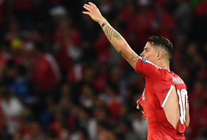 Switzerland's midfielder Granit Xhaka in a ripped shirt gestures during the Euro 2016 group A football match between Switzerland and France at the Pierre-Mauroy stadium in Lille on June 19, 2016. / AFP PHOTO / FRANCK FIFE