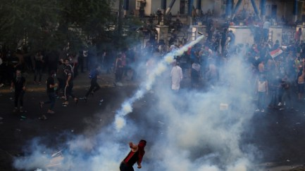 An Iranian demonstrator in Baghdad throws a tear gas canister used by Iraqi security forces