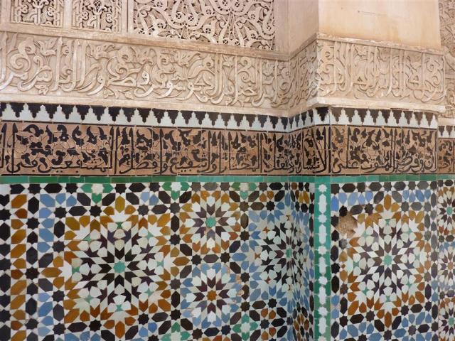 In Tijd en slijt staat de taligheid van het gebouw centraal, de metafoor van het gebouw als een boek bij de Medersa Ben Youssef | Ben Joesoefmadrassa te Marrakesh. Een symboliek die oost en west delen! Hier zie je de kalligrafie van gewijde en andere teksten gebeiteld en gebakken in steen. Foto bvhh.nu 2014.