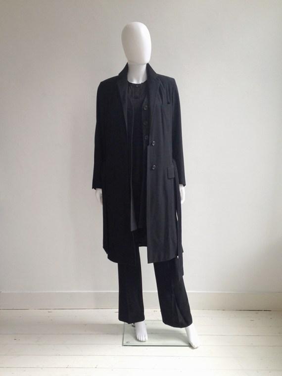 Dries Van Noten black long belted coat | Dries Van noten black waistcoat | Ann Demeulemeester black trousers | Nicolas Andreas Taralis black muscle tee | shop at vaniitas.com