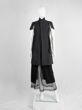 Comme des Garçons black deconstructed jacket with cut off sleeves sewn on the sides — spring 2012