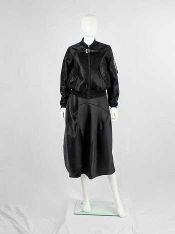 Noir Kei Ninomiya black bomber jacket with belted strap across the chest