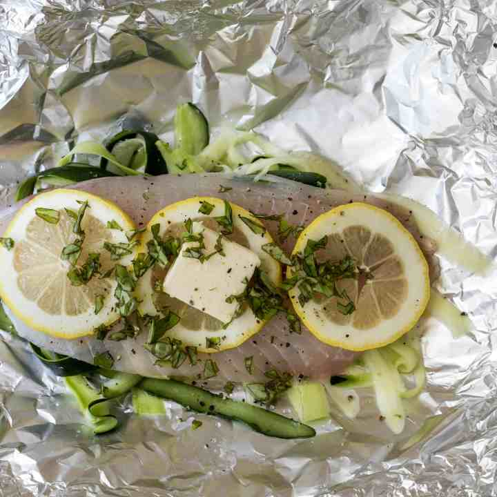 tilapia fillet on tin foil with shaved zucchini ribbons, butter, and lemon slices