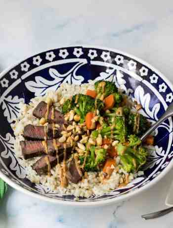 grain bowl with steak, brown rice, broccoli, carrots, and peanut sauce in blue bowl with green napkin
