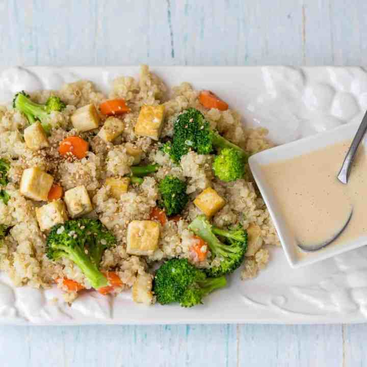 quinoa grain bowl with broccoli, carrots, tofu, and sesame-ginger dressing