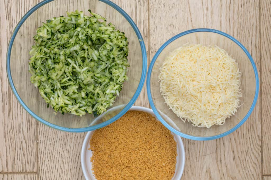 bowls of ingredients for zucchini gratin: shredded zucchini, cheese, and seasoned breadcrumbs