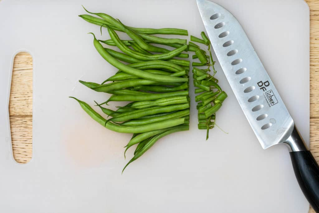 Trimming green beans on cutting board with knife
