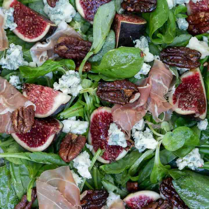 close up of fig salad with blue cheese, pecans, and proscuitto
