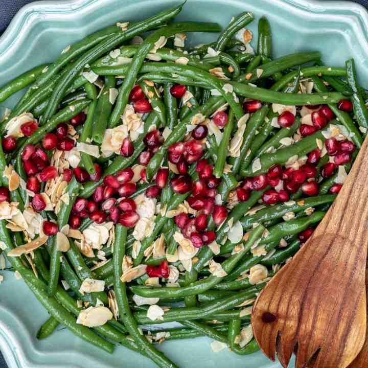green beans almondine with pomegranate seeds in large bowl with serving tongs