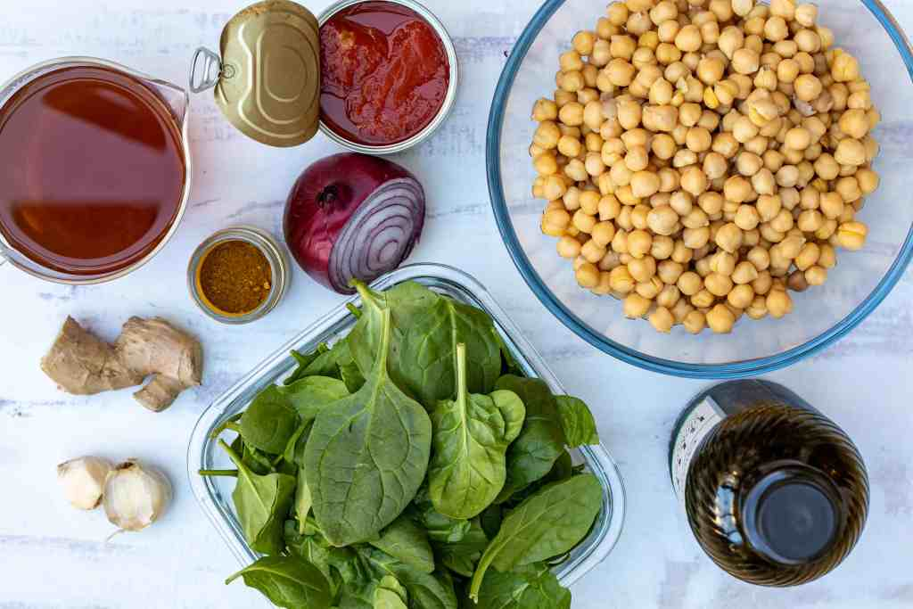 ingredients for vegan chickpea curry: chickpeas, spinach, canned tomatoes, olive oil, onion, curry powder, ginger, garlic, vegetable broth