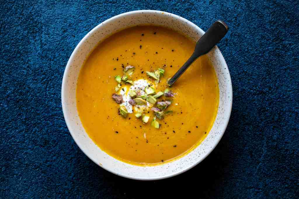 bowl of carrot ginger soup with creme fraiche and pistachios