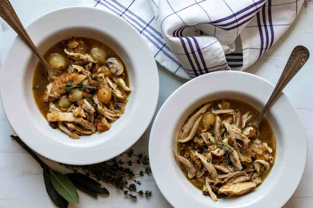 two bowls of coq au vin blanc with herbs and kitchen towel