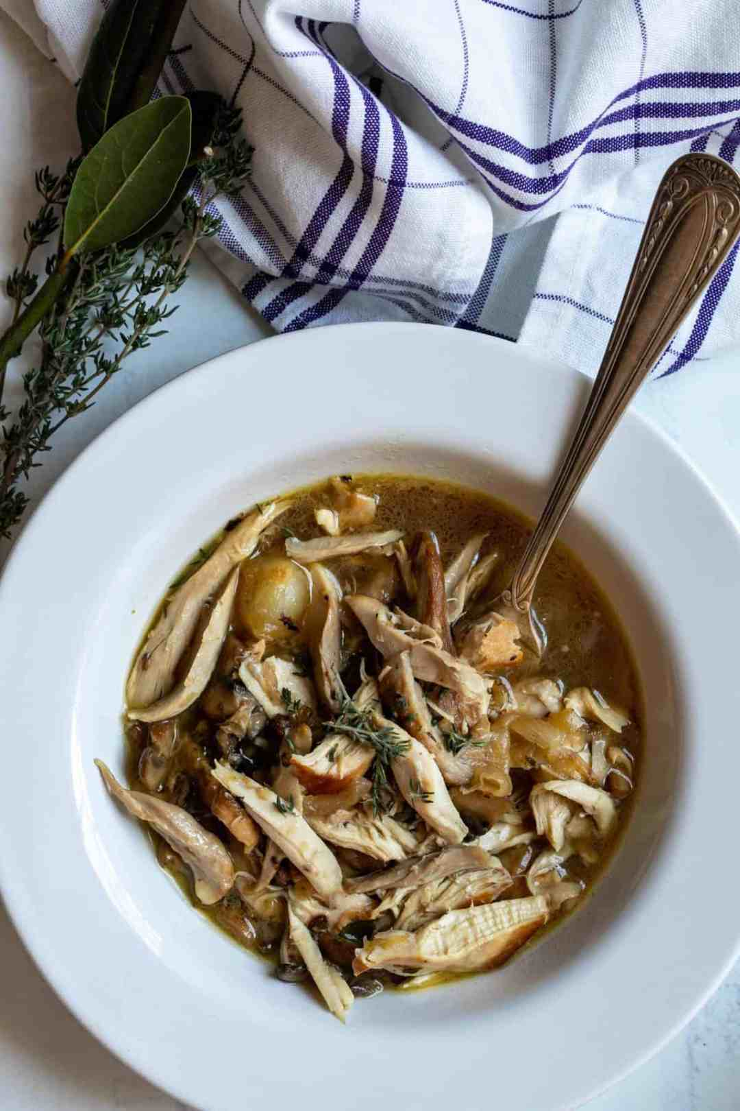 coq au vin blanc with towel and thyme sprig