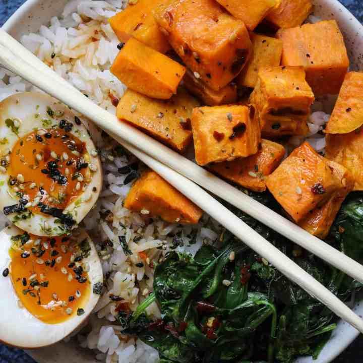 Close up of ramen egg rice bowl with chopsticks