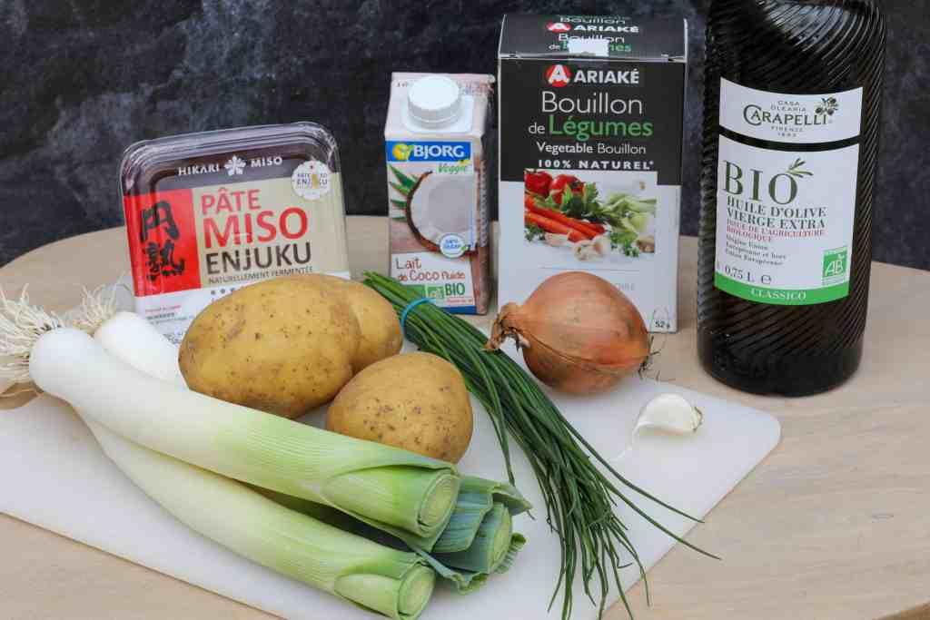 Ingredients for vegan potato leek soup: leeks, potatoes, chives, garlic, miso paste, coconut milk, onion, vegetable broth, and olive oil