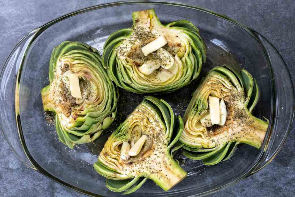 four artichoke halves seasoned, stuffed with garlic cloves and drizzled with oil in glass baking dish