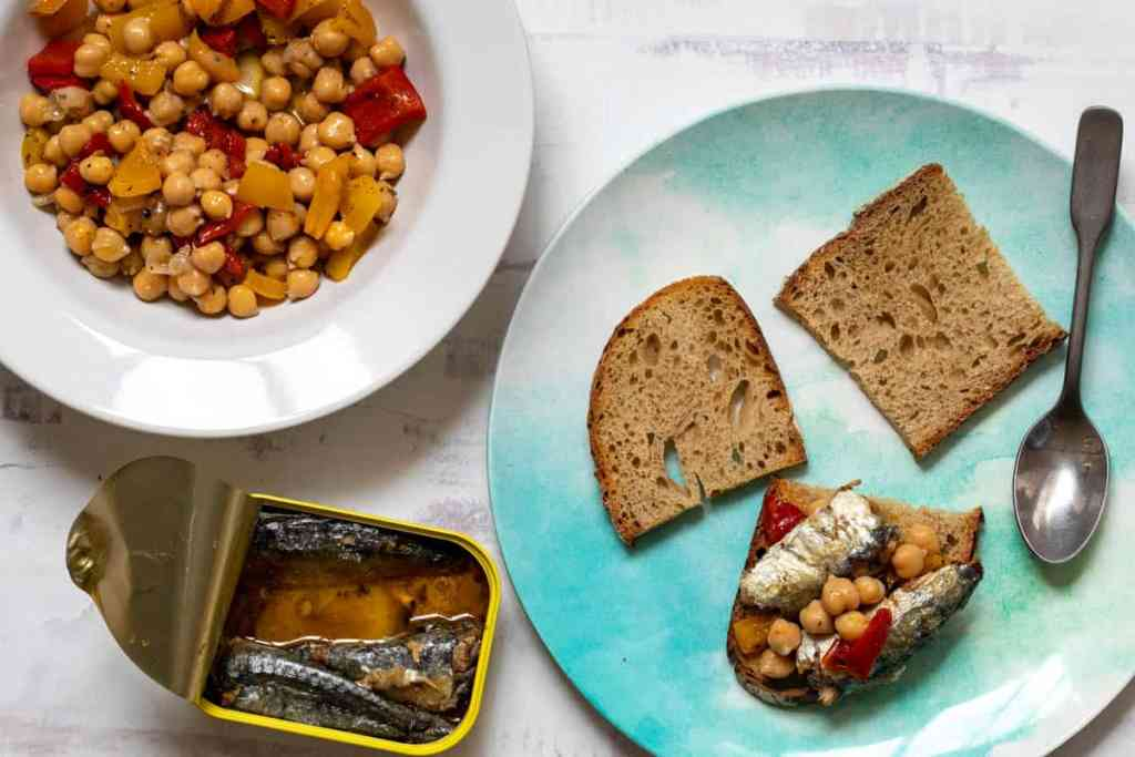 bowl of chickpea and roasted pepper salad and sardine tin next to plate with toasts being assembled