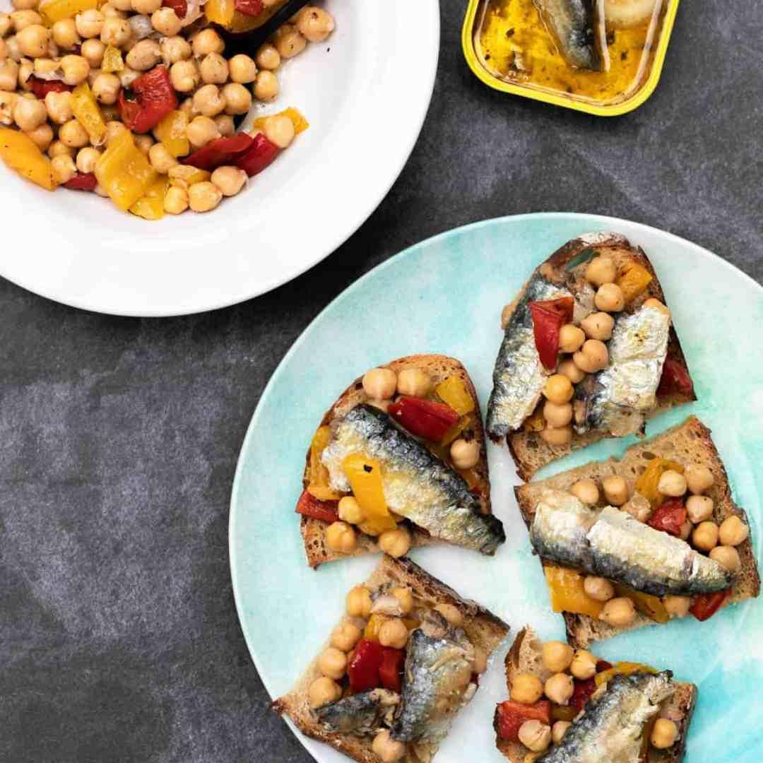 sardines on toast with chickpea salad on plate next to bowl of chickpea salad and sardine tin