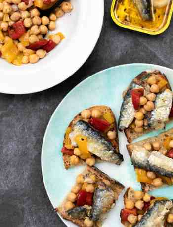 sardines on toast with chickpea salad on plate next to bowl of chickpea salad and sardine tin