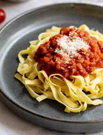 plate of lentil bolognese on fettuccine noodles with cherry tomatoes in background