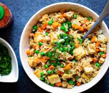 tofu fried rice in bowl next to small bowl of scallions and bottle of sriracha