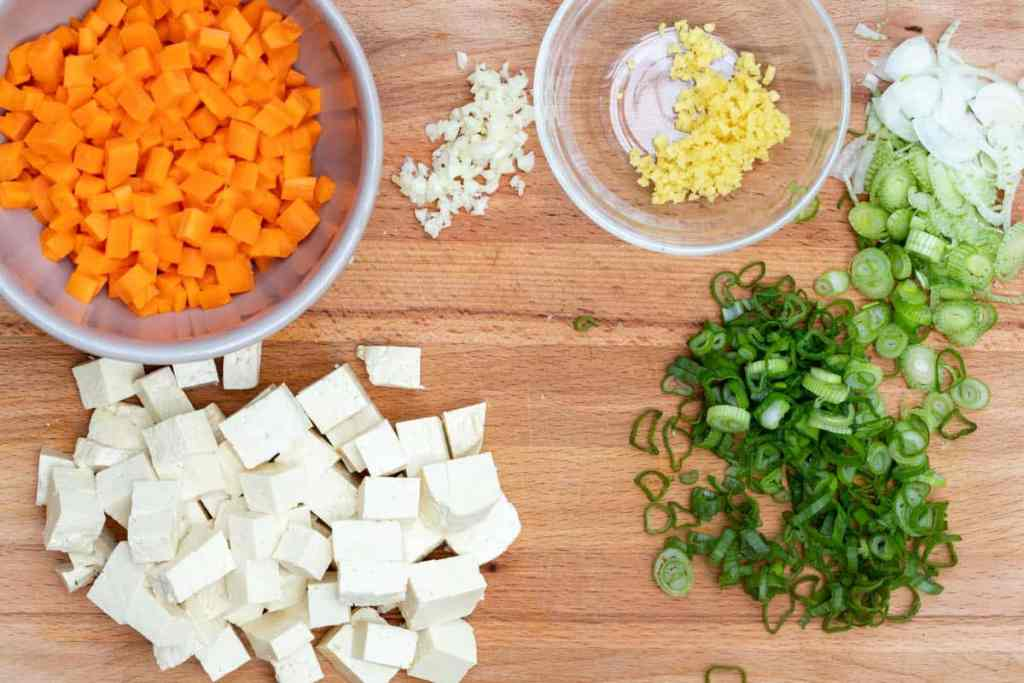 bowl of chopped carrots, bowl of chopped ginger, plus chopped tofu, garlic, and scallions