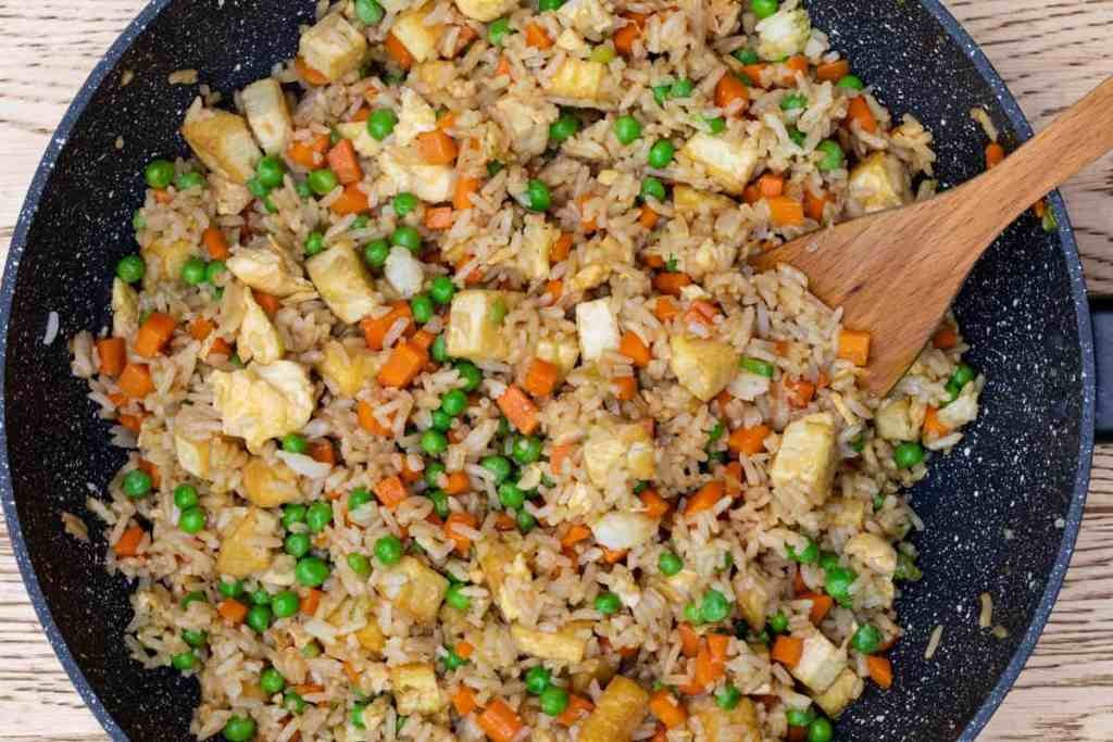 tofu fried rice in wok with wooden spatula